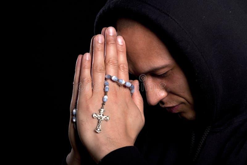Jonge mens het bidden stock afbeelding