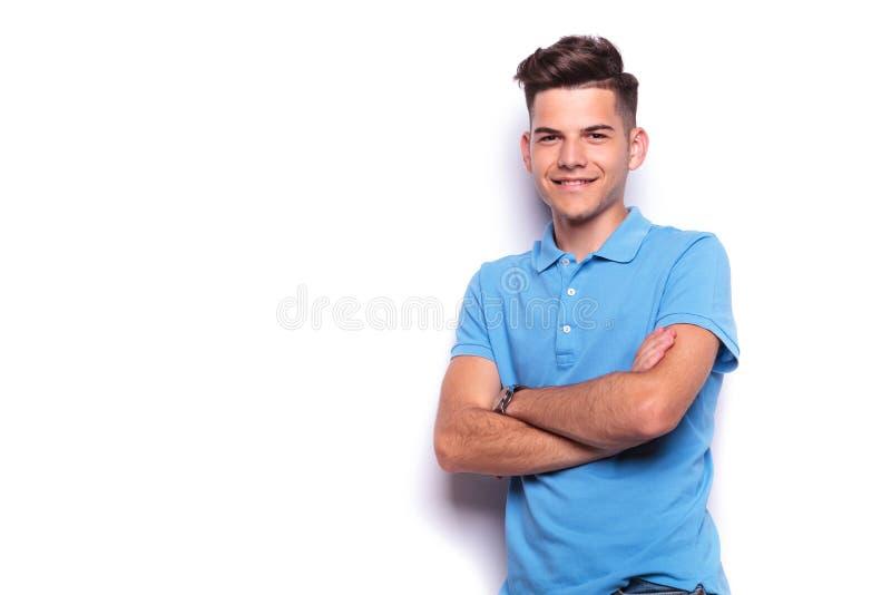 Jonge mens in het blauwe polooverhemd stellen in witte studio stock afbeeldingen