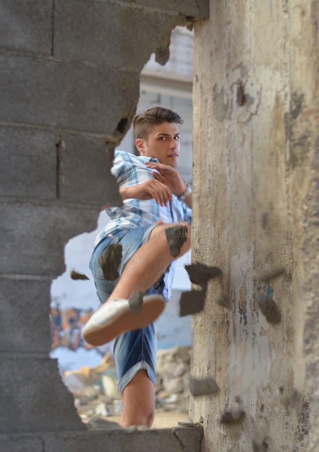 Jonge mens het breken door muur met een schop royalty-vrije stock afbeeldingen