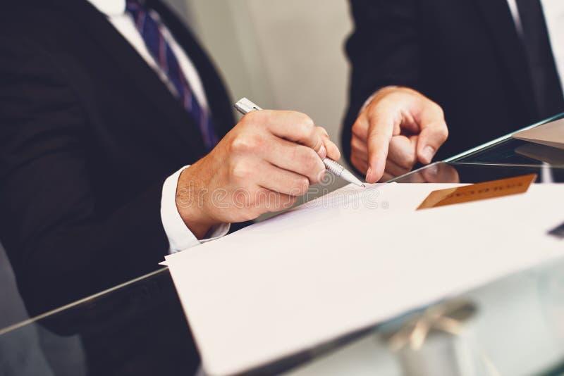 Jonge mens het document ondertekenen en zijn partner die aan het richten royalty-vrije stock afbeelding