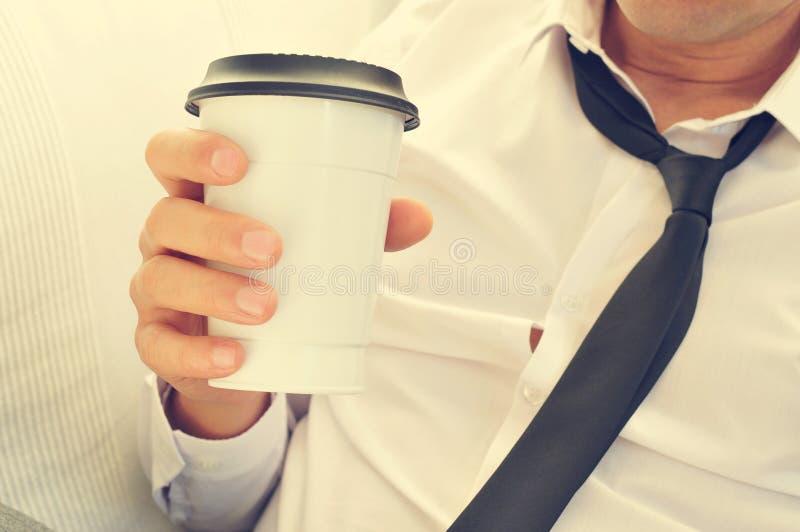 Jonge mens het drinken koffie in een document kop stock foto's