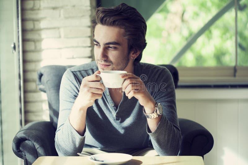 Jonge mens het drinken koffie in koffie stock afbeeldingen