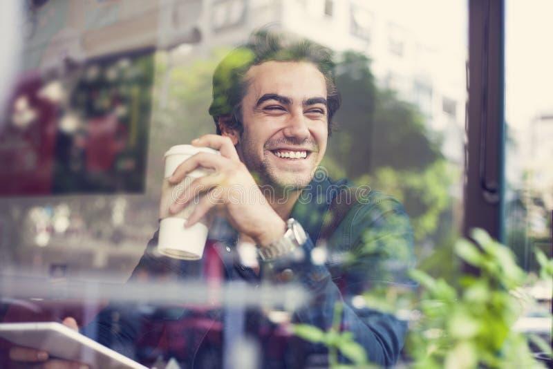 Jonge mens het drinken koffie in koffie royalty-vrije stock fotografie