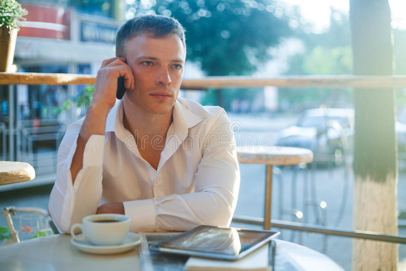 Jonge mens het drinken koffie in koffie en het gebruiken van telefoon stock fotografie
