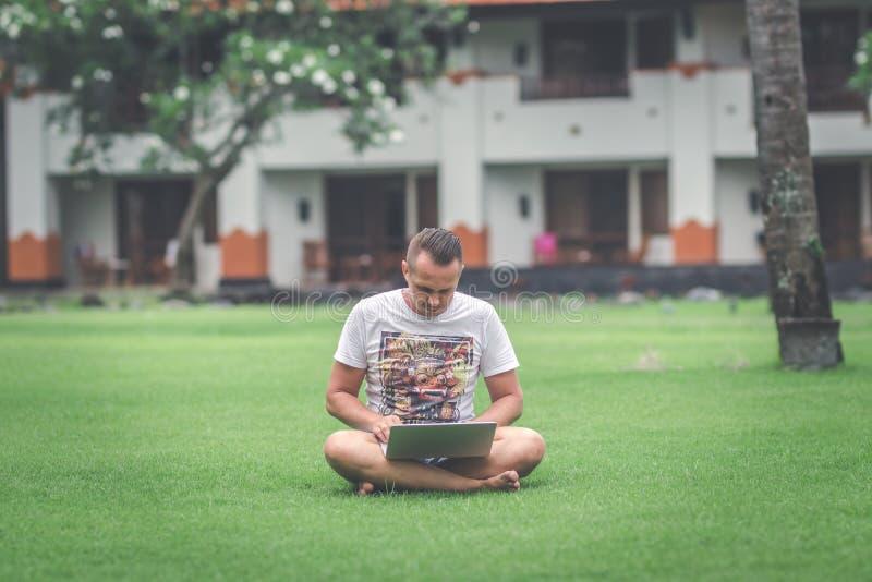 Jonge mens in het groene tropische park die online met laptop werken Freelancermens op het eilandconcept van Bali royalty-vrije stock foto's