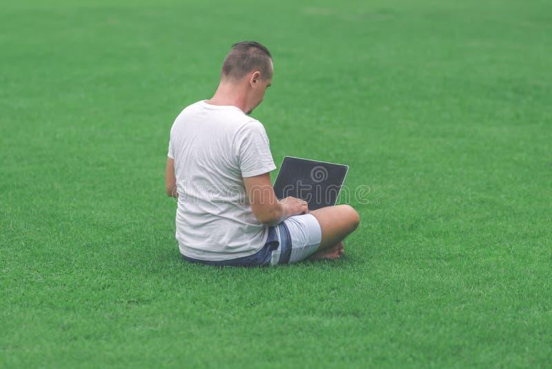 Jonge mens in het groene tropische park die online met laptop werken Freelancermens op het eilandconcept van Bali stock foto's