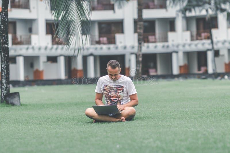 Jonge mens in het groene tropische park die online met laptop werken Freelancermens op het eilandconcept van Bali stock afbeeldingen