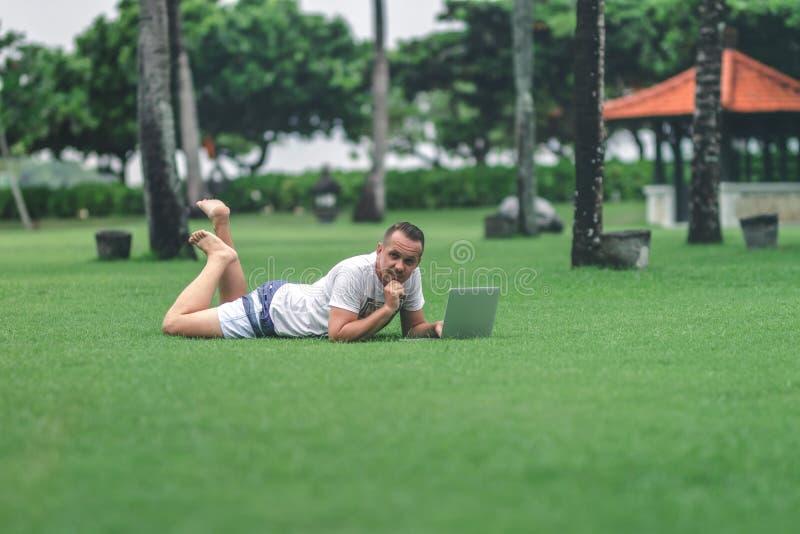 Jonge mens in het groene tropische park die online met laptop werken Freelancermens op het eilandconcept van Bali royalty-vrije stock afbeelding