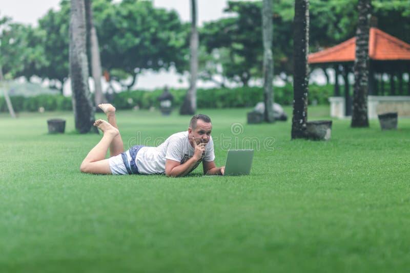 Jonge mens in het groene tropische park die online met laptop werken Freelancermens op het eilandconcept van Bali stock afbeelding