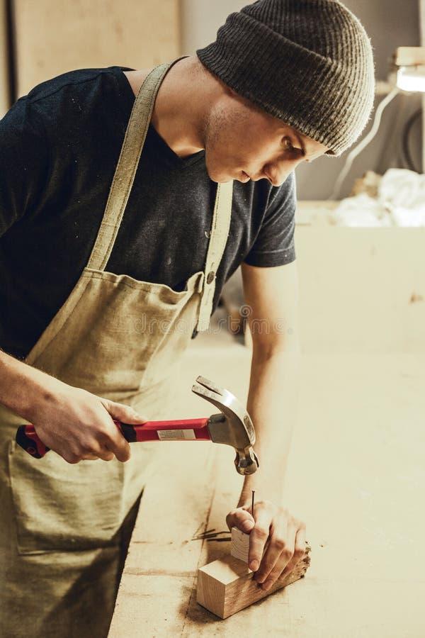 Jonge mens het hameren spijker in hout stock afbeeldingen