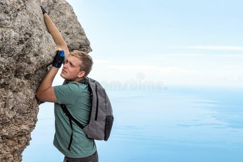 Jonge mens het hangen op rand, beklimt op de rots royalty-vrije stock foto