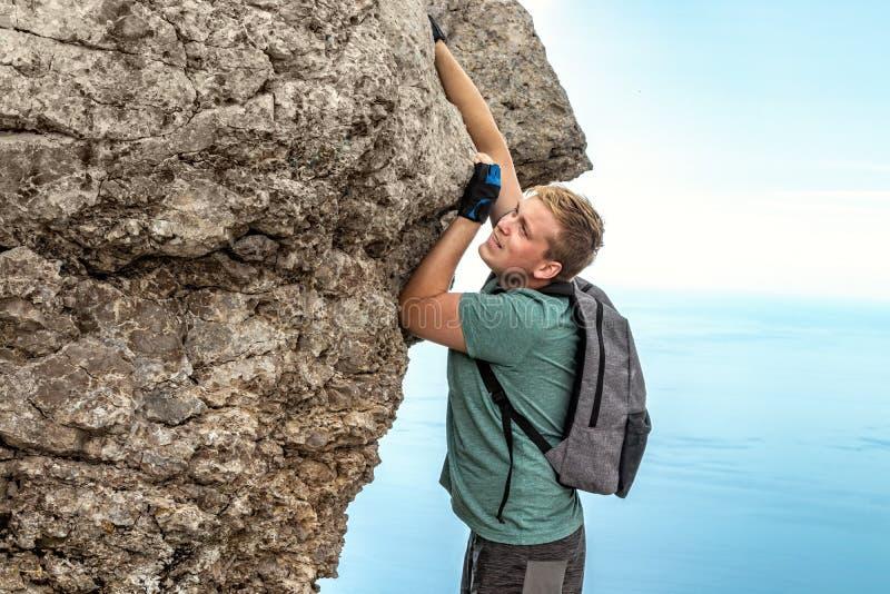 Jonge mens het hangen op rand, beklimt op de rots royalty-vrije stock afbeeldingen