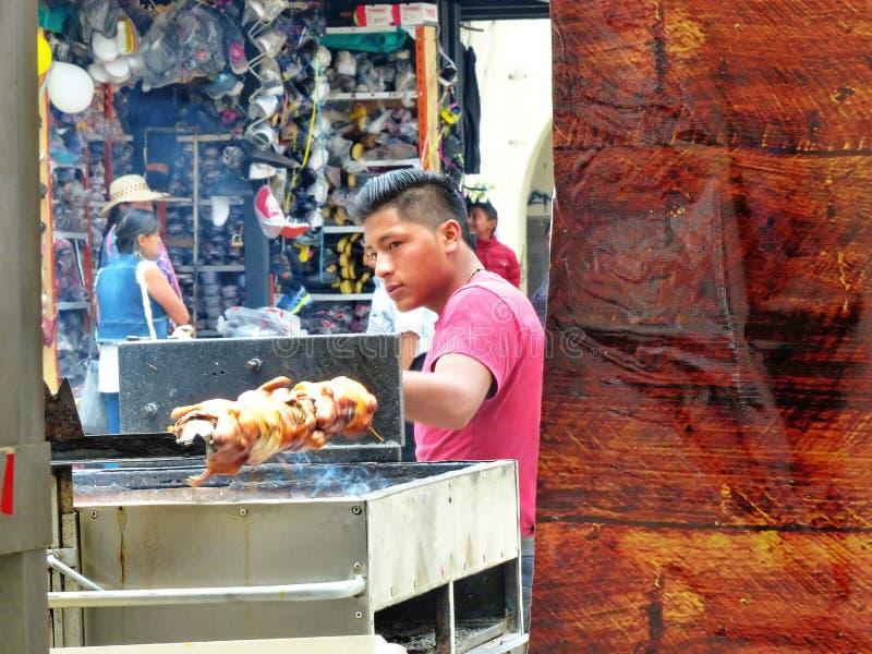 Jonge mens het koken op grill geroosterde cuy, Ecuador royalty-vrije stock fotografie