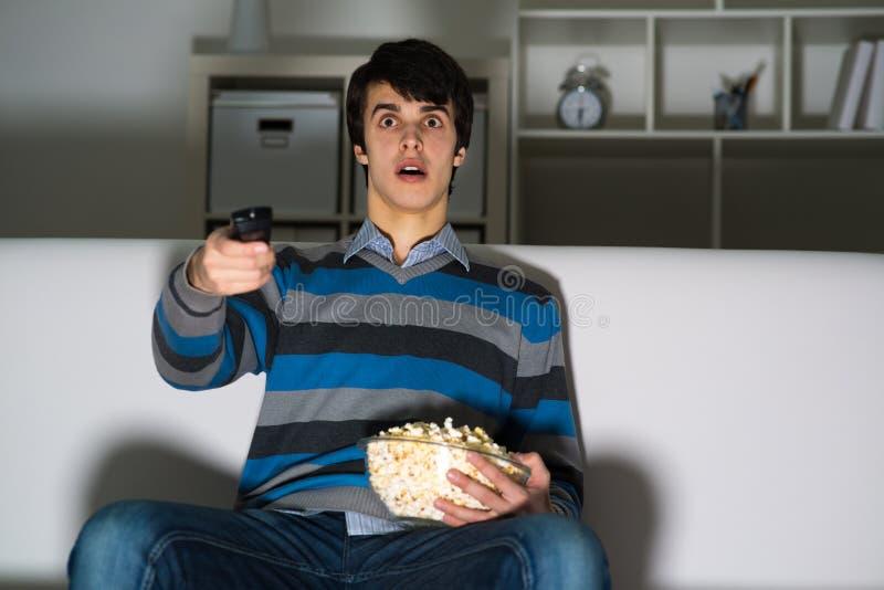 Jonge mens het letten op televisie met popcorn stock foto's