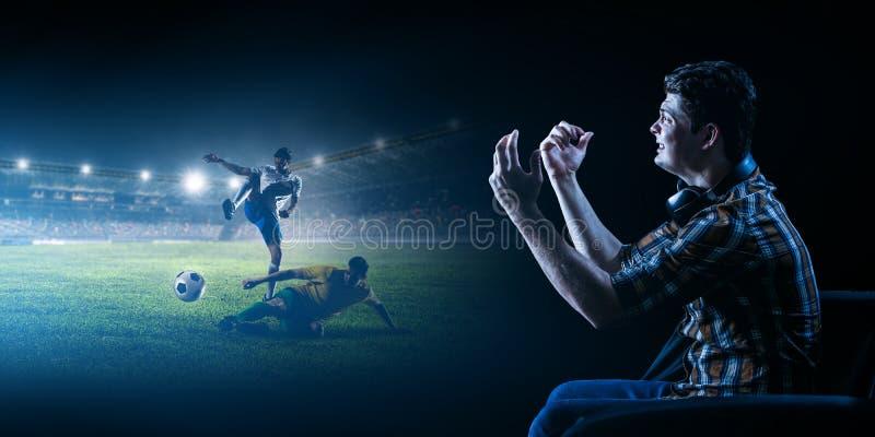 Jonge mens het letten op voetbal op het grote scherm royalty-vrije stock fotografie