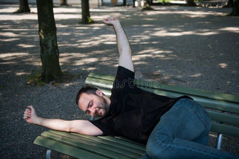 Jonge mens het liggen slaap op bank in het park en kielzog omhoog na rust royalty-vrije stock fotografie