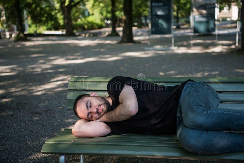 Jonge mens het liggen slaap op bank in het park en kielzog omhoog na rust stock fotografie