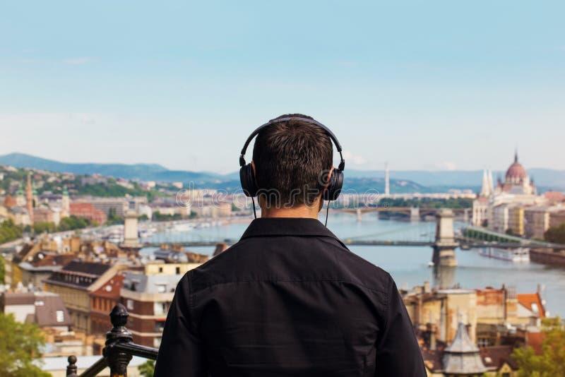 Jonge mens het luisteren muziek achtermening met Boedapest royalty-vrije stock afbeeldingen