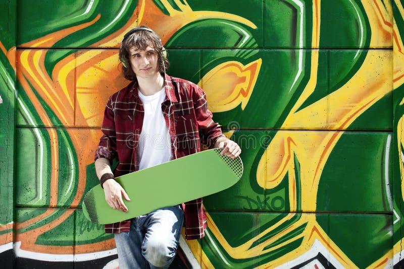 Jonge mens het luisteren muziek dichtbij een graffitimuur stock foto