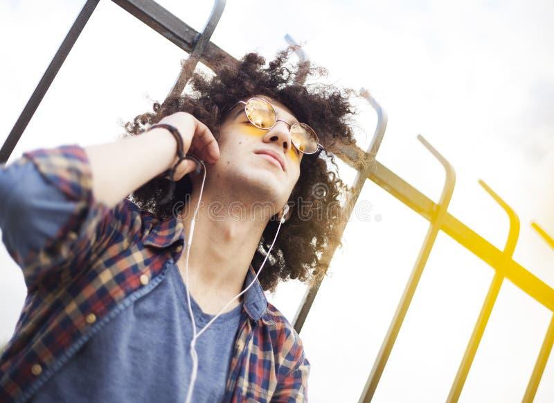 Jonge mens het luisteren muziek met oortelefoons stock fotografie