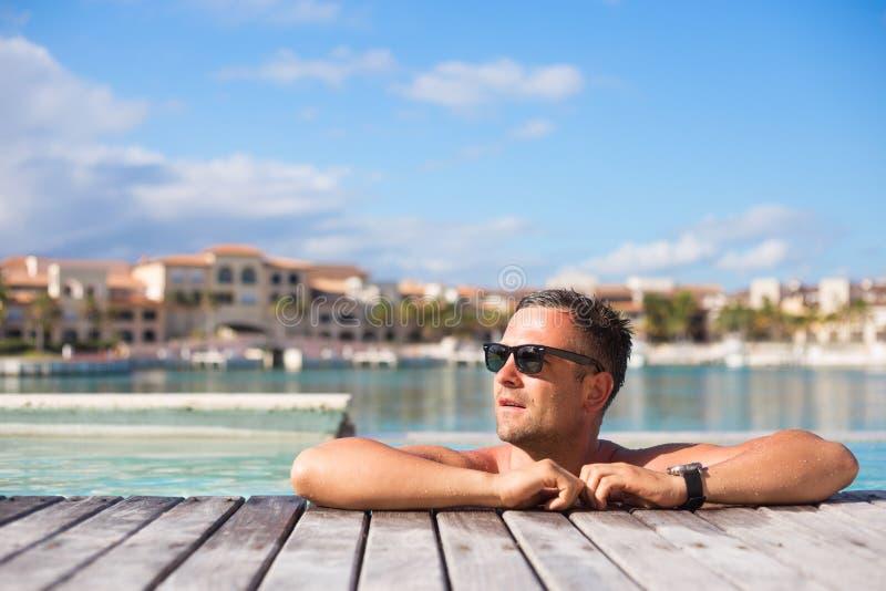 Jonge mens het ontspannen in het zwembad royalty-vrije stock afbeeldingen