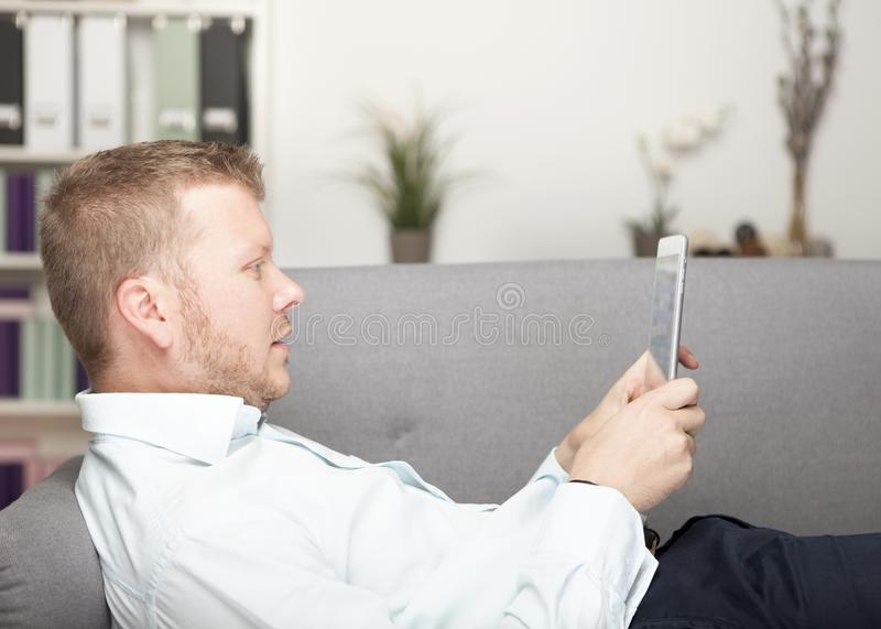 Jonge mens het ontspannen met een tabletcomputer stock fotografie