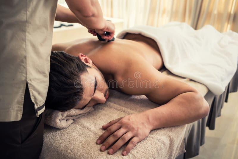 Jonge mens het ontspannen tijdens traditionele massage met hete stenen royalty-vrije stock afbeeldingen