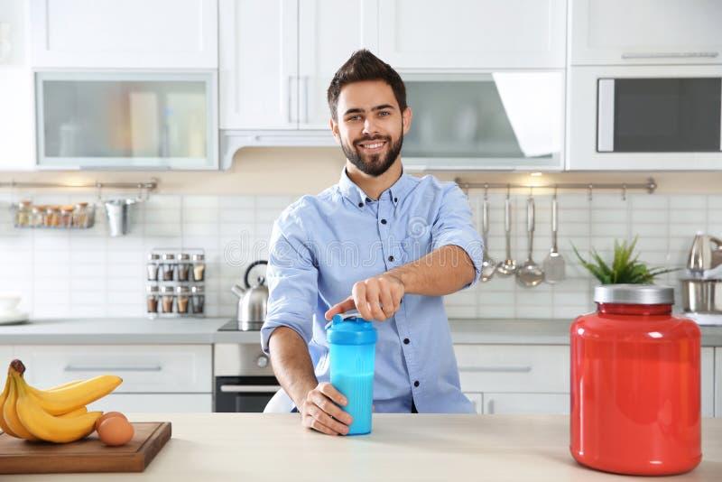 Jonge mens het openen fles van eiwitschok bij lijst met ingrediënten royalty-vrije stock afbeelding