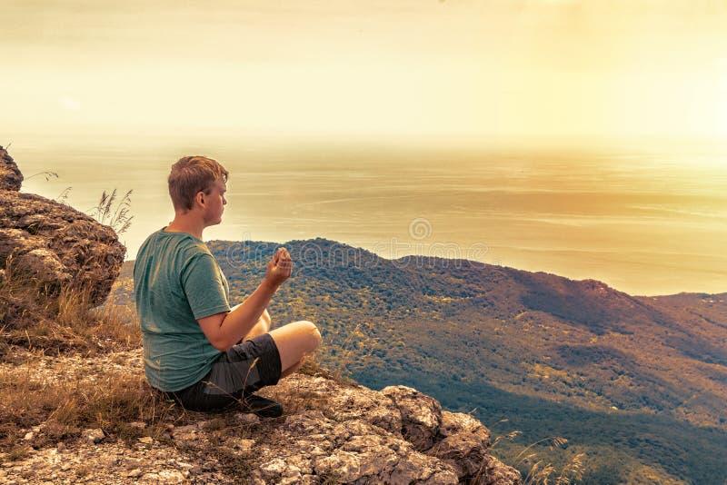 Jonge mens het praktizeren de yoga stelt zitting op de rotsachtige piek De mens doet meditatie en het genieten van van mening royalty-vrije stock afbeelding