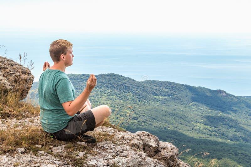 Jonge mens het praktizeren de yoga stelt zitting op de rotsachtige piek De mens doet meditatie en het genieten van van mening royalty-vrije stock fotografie