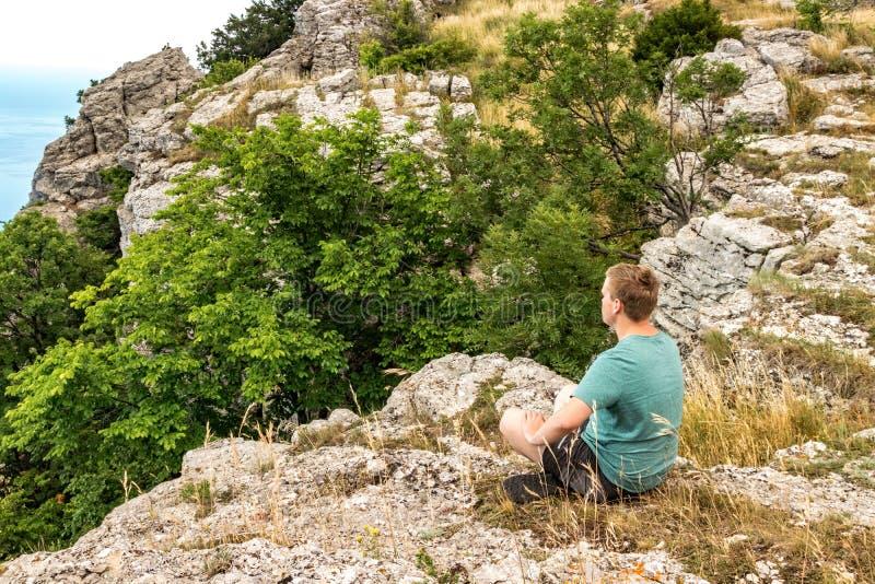 Jonge mens het praktizeren de yoga stelt zitting op de rotsachtige piek De mens doet meditatie en het genieten van van mening royalty-vrije stock afbeeldingen