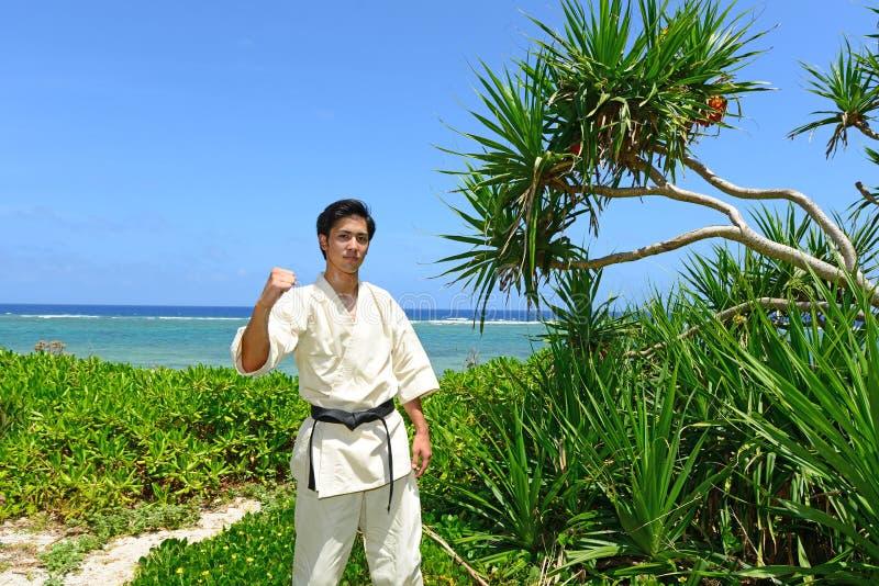 Jonge mens het praktizeren karate bij strand royalty-vrije stock fotografie