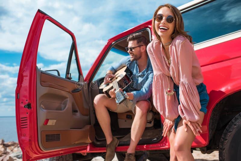 jonge mens het spelen gitaar dichtbij auto met vrolijk meisje stock fotografie
