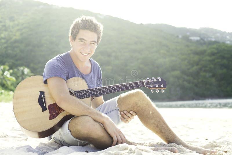Jonge mens het spelen gitaar op het strand royalty-vrije stock afbeelding
