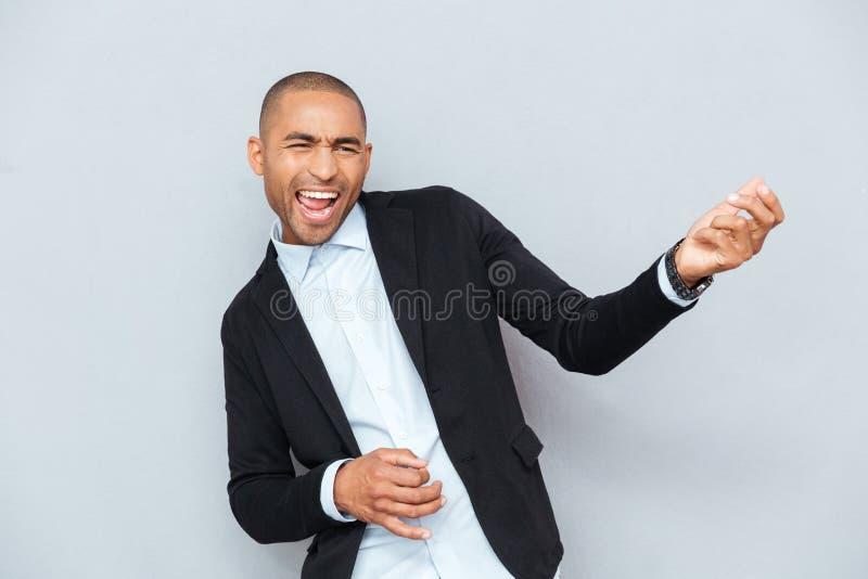 Jonge mens het spelen luchtgitaar over grijze achtergrond royalty-vrije stock fotografie
