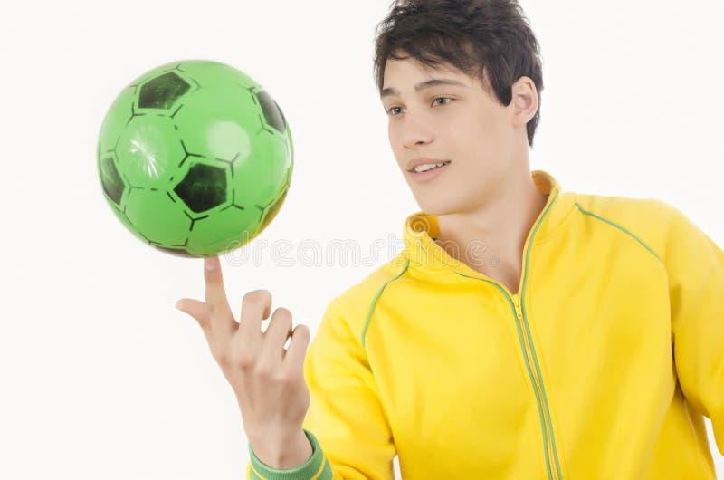 Jonge mens het spelen met een voetbalbal stock foto's
