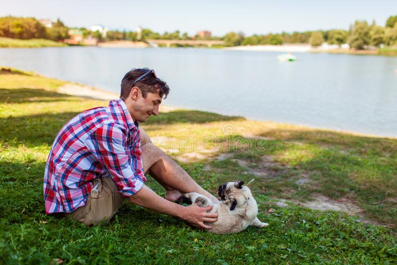Jonge mens het spelen met pug hondzitting op gras Gelukkig puppy die pret met meester hebben royalty-vrije stock afbeeldingen