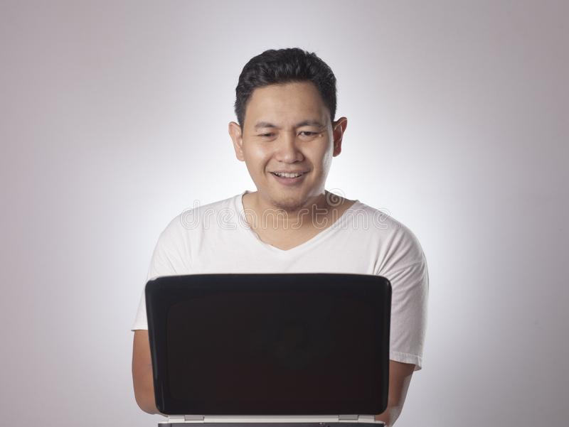 Jonge Mens het Spelen met Zijn Laptop, het Glimlachen Uitdrukking stock foto's