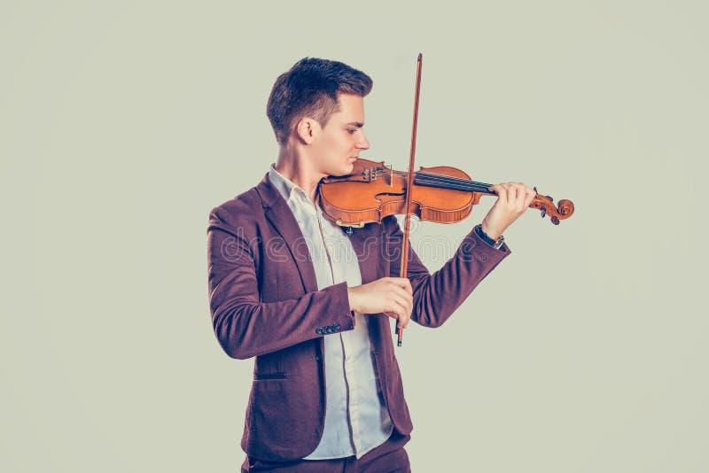 Jonge mens het spelen op houten viool stock afbeeldingen