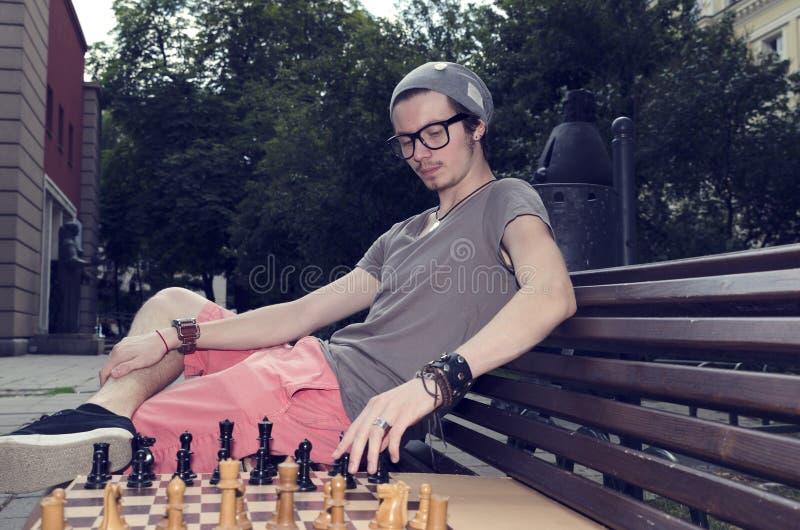 Jonge mens het spelen schaak in het park Het zitten op een bank maakt hij een beweging royalty-vrije stock foto's
