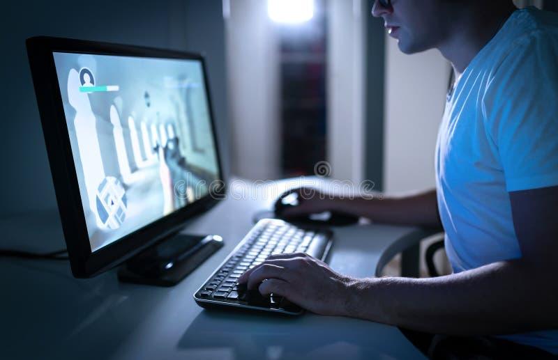 Jonge mens het spelen videospelletje laat bij nacht thuis Gamer stromend fps videospelletje online Eerste Person Shooter royalty-vrije stock foto