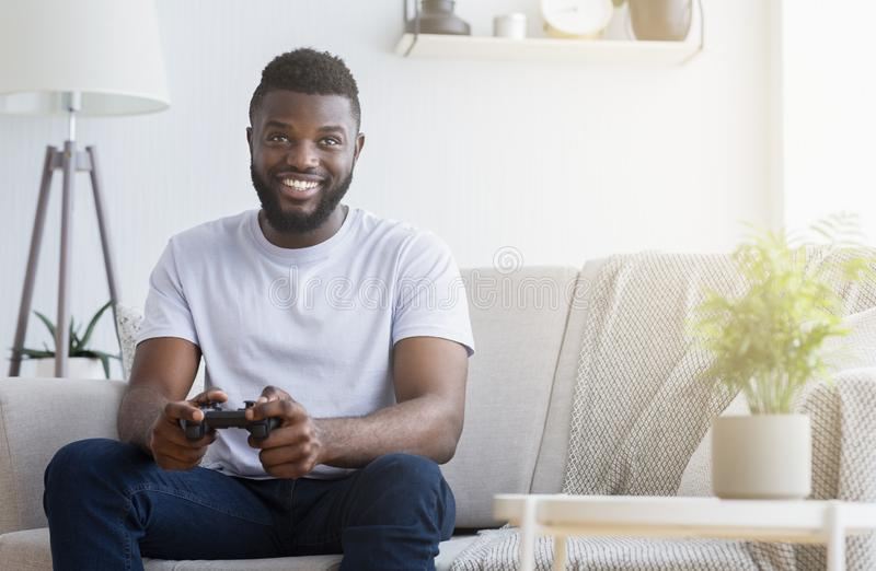 Jonge mens het spelen videospelletjes thuis stock foto's