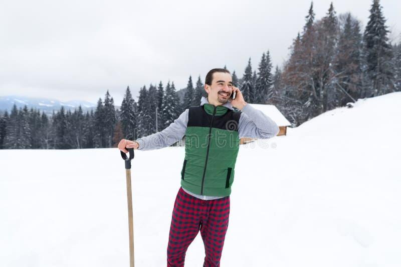 Jonge Mens het Spreken Sneeuwdorp van de Cel het Slimme Telefoon het Houten Plattelandshuisje van de de Sneeuwtoevlucht van de Bu stock fotografie