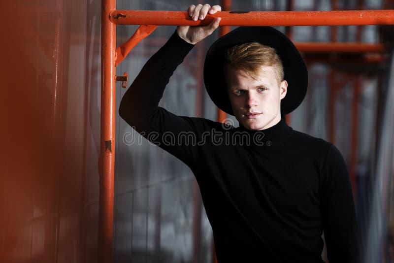 Jonge mens het stellen met een in uitrusting tegen een stedelijke achtergrond stock fotografie