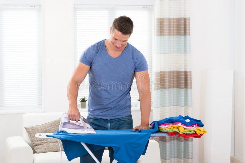Jonge mens het strijken kleren stock foto's