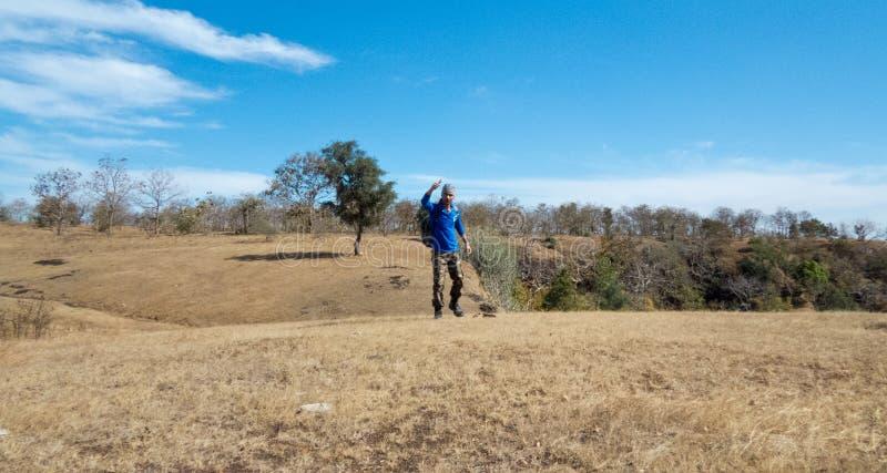 Jonge mens het tonen klopt omhoog na met succes het bereiken van heuvel/berg` s piek royalty-vrije stock foto's