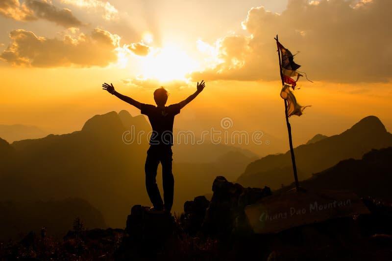 Jonge mens het uitspreiden handen met vreugde en inspiratie op berg royalty-vrije stock afbeelding