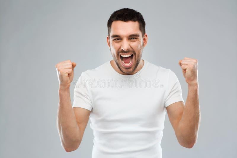 Jonge mens het vieren overwinning over grijs stock foto