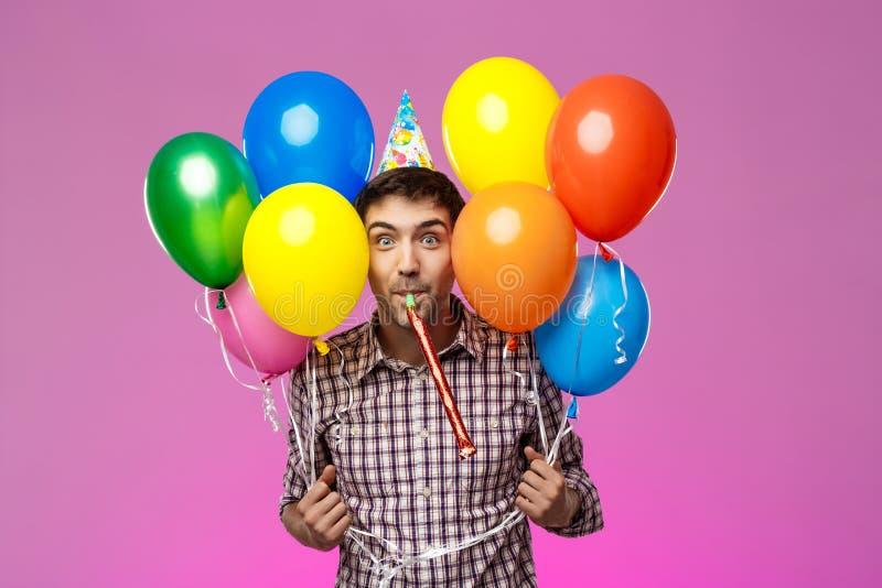 Jonge mens het vieren verjaardag, die kleurrijke baloons over purpere achtergrond houden royalty-vrije stock foto