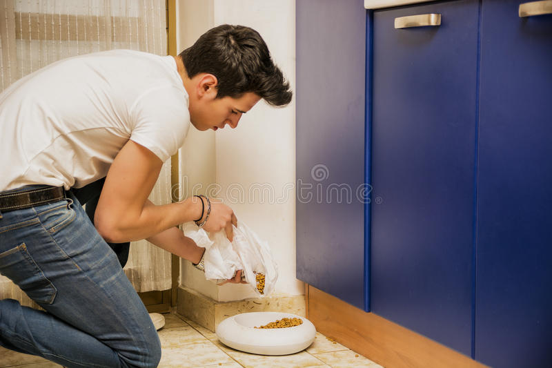 Jonge Mens het Vullen Huisdierenkom met Droog Voedsel stock fotografie